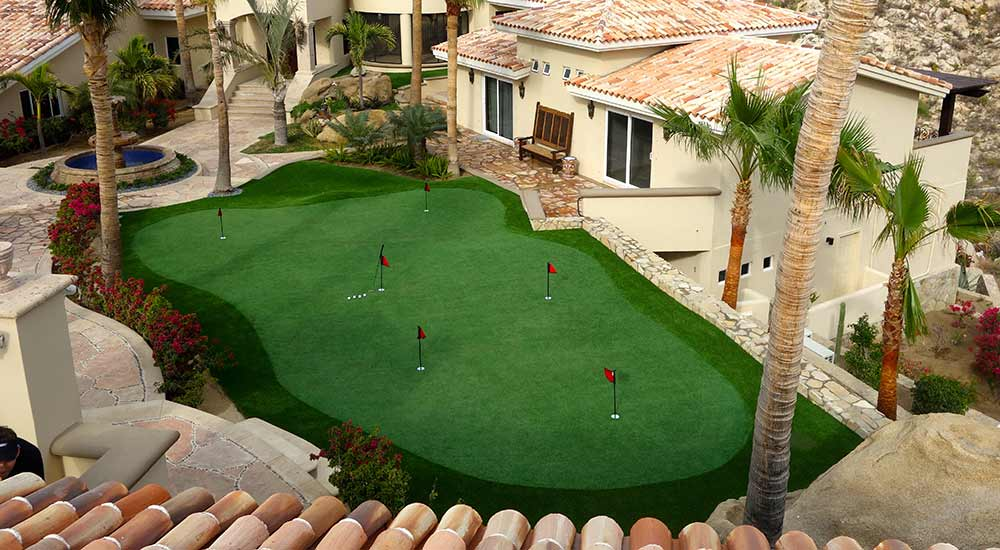 Golf green made from artificial grass, surrounded by palm trees and villas