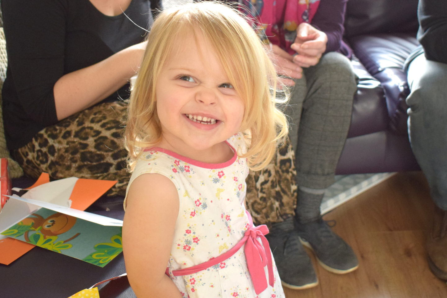 Two year old in a party dress, smiling at the camera