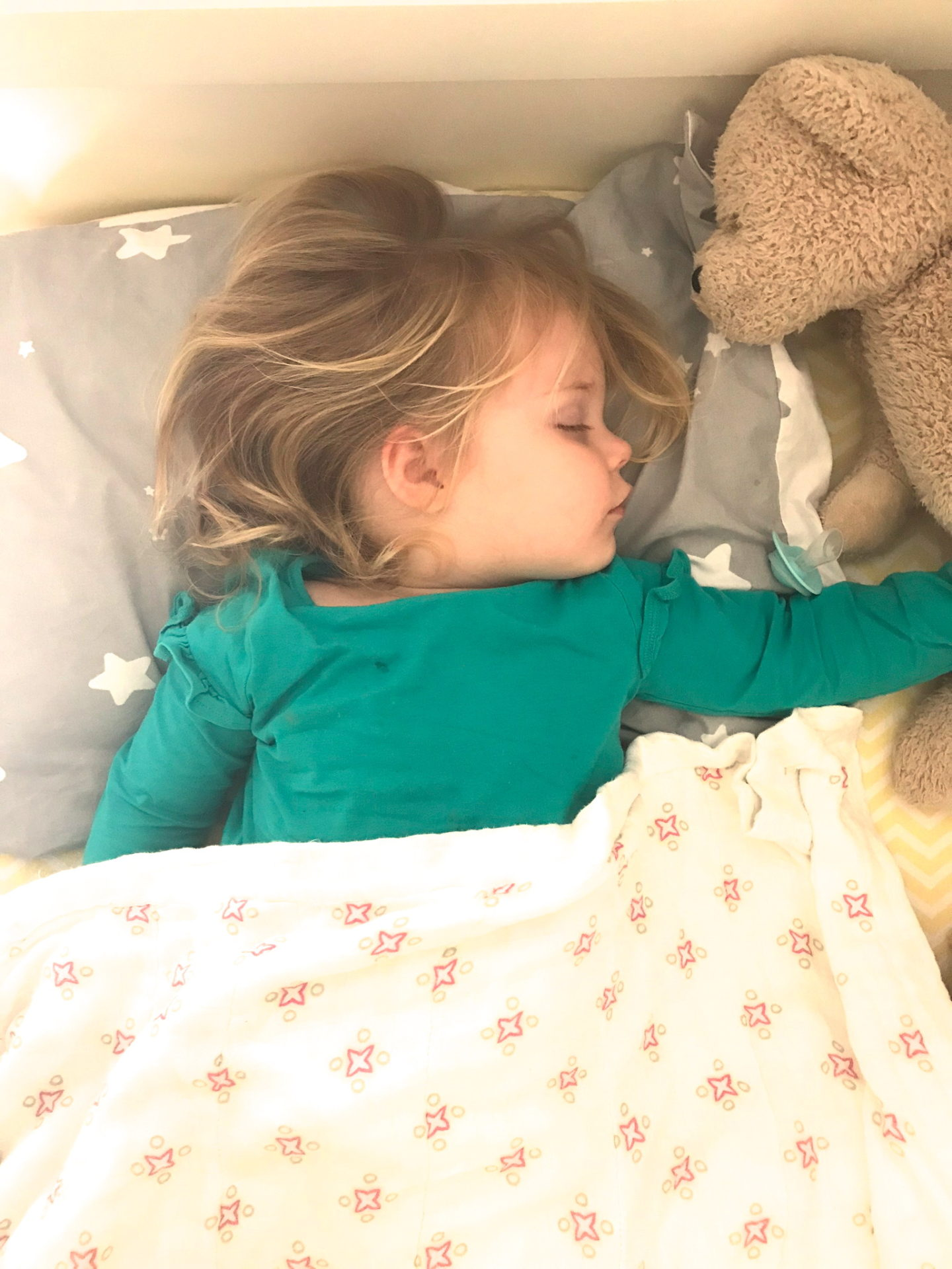 Two year old sleeping in bed with teddy