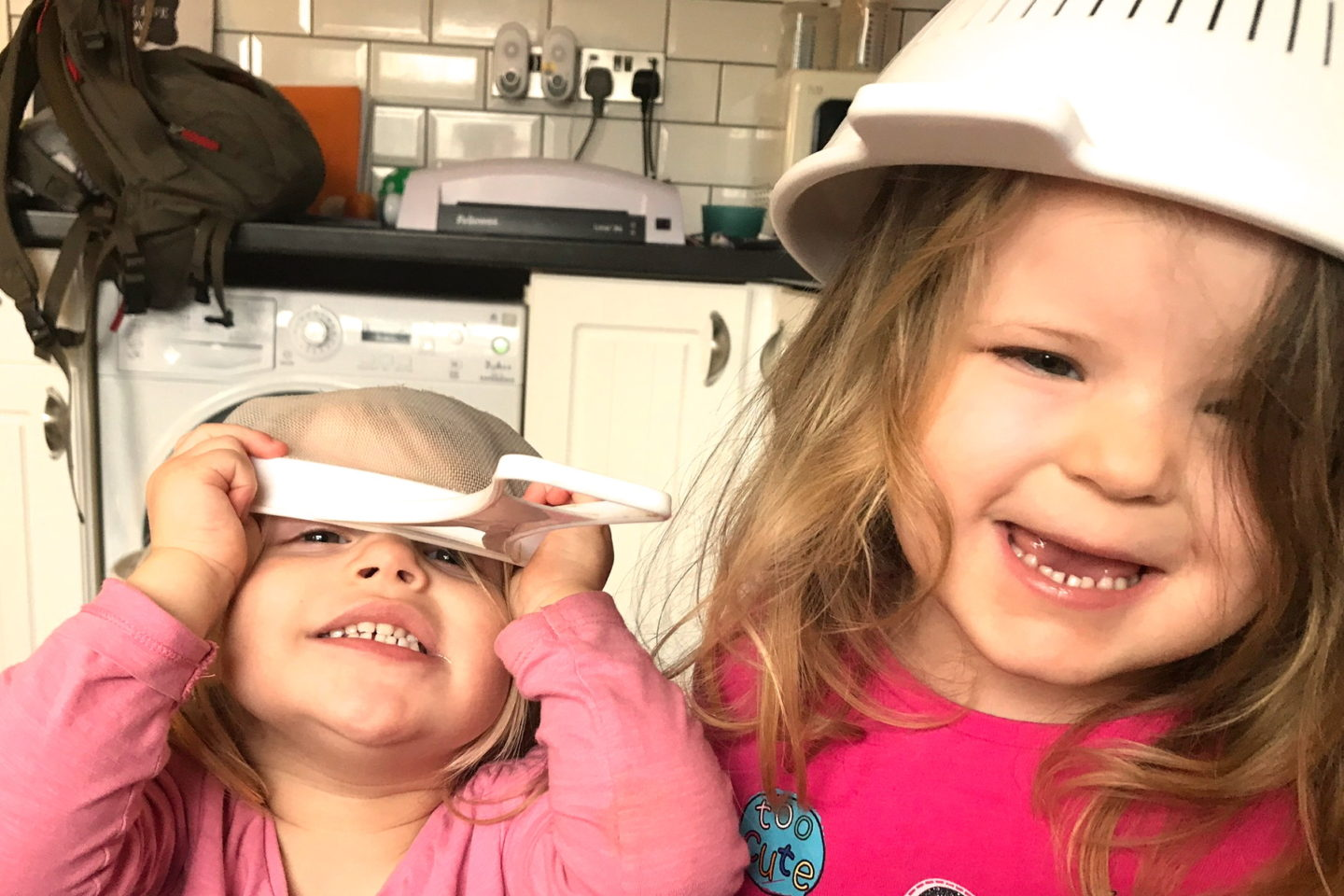 two young sisters laughing with sieves on their heads