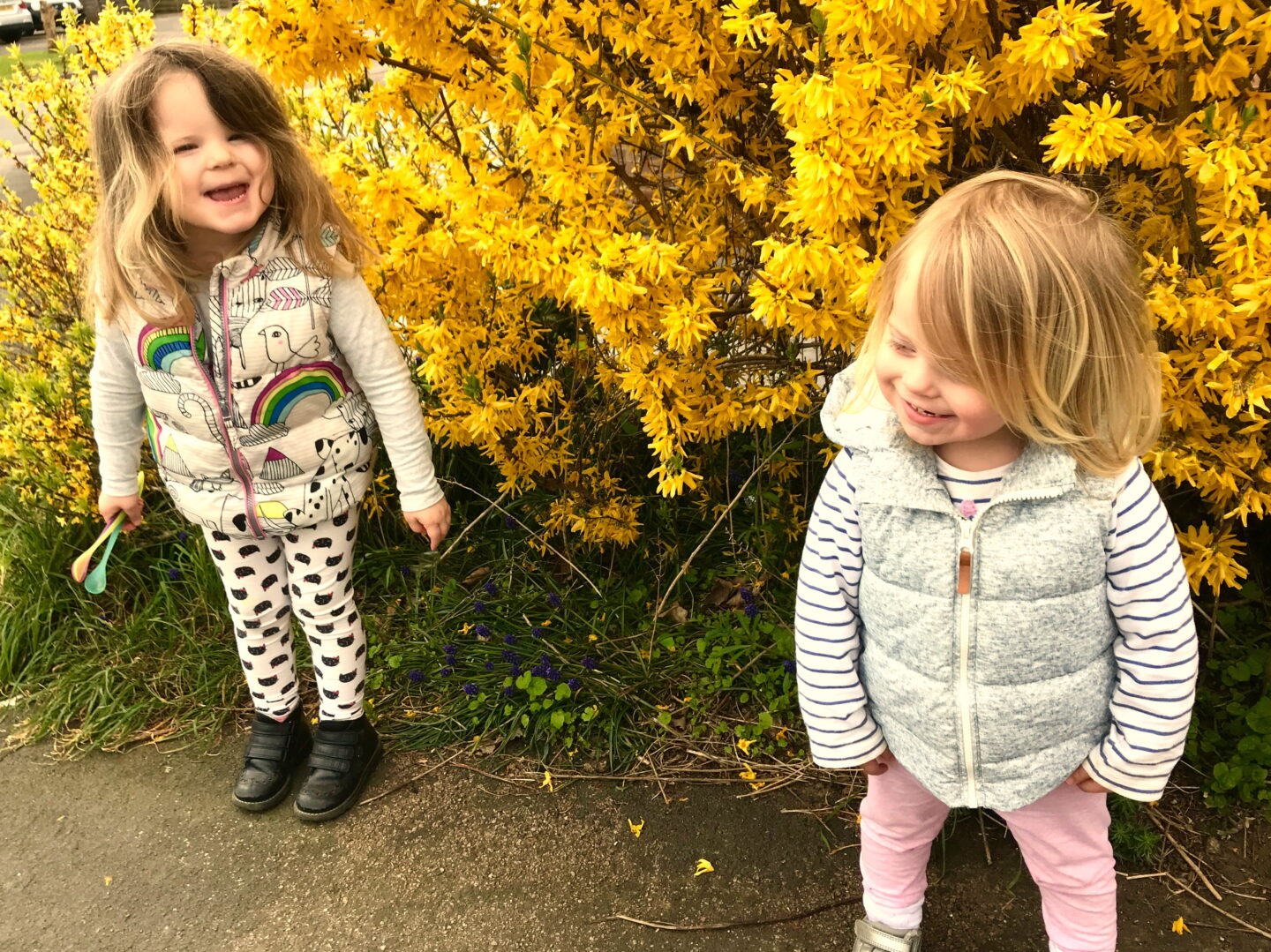 Two sisters standing in front of a yellow flowering bush, smiling