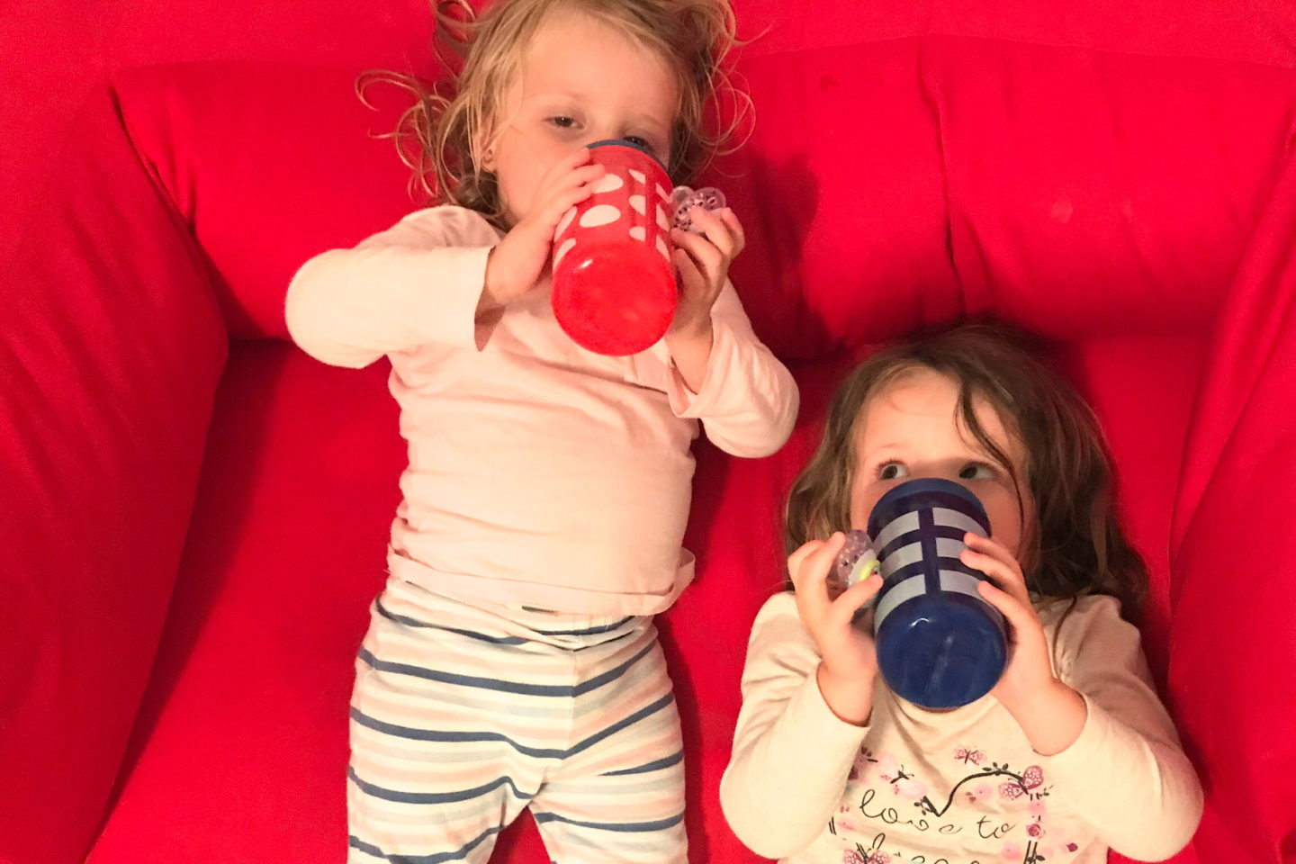 Two sisters in pyjamas, drinking milk, lying on a sofa
