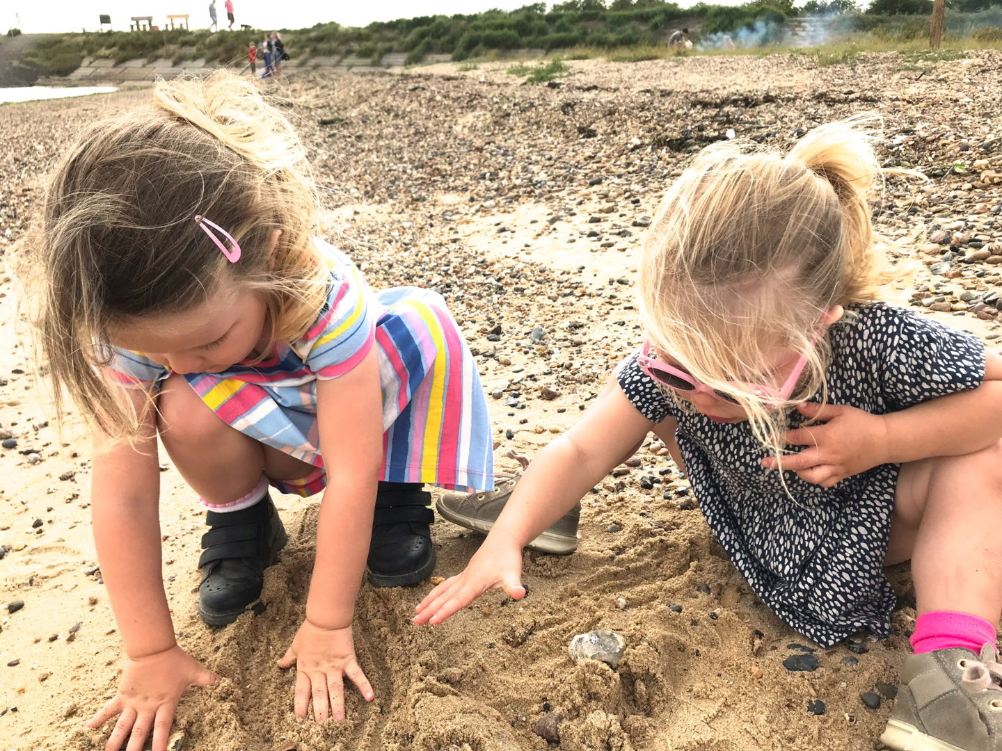 two sisters playing in the sand together