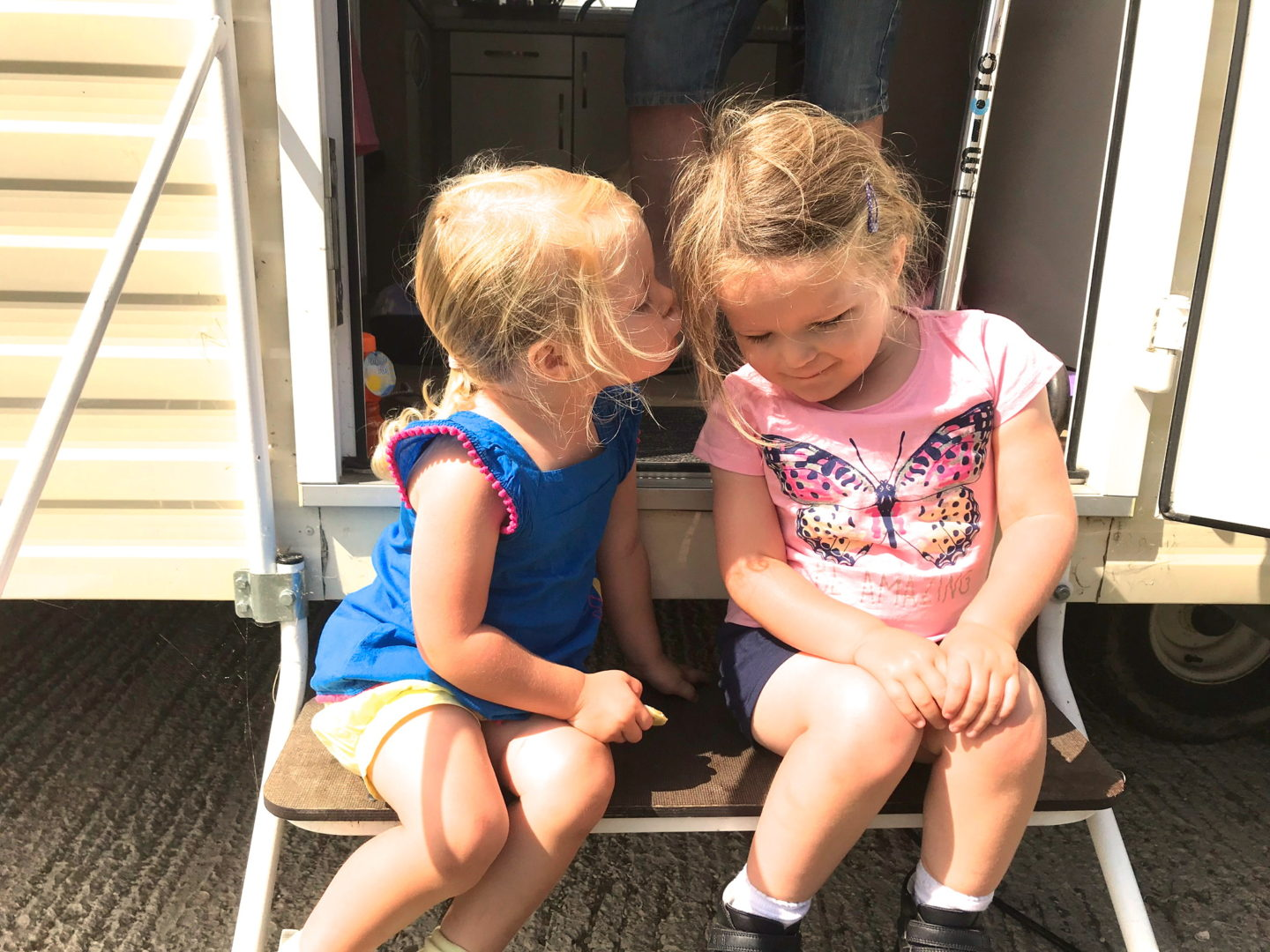 two little sisters sitting on the steps of a caravan, one kissing the other's cheek