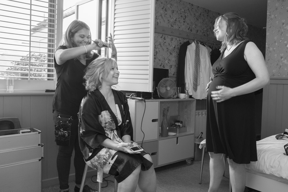 bride laughs and chats to pregnant bridesmaid while having her hair styled at Brooks Guesthouse in Bristol