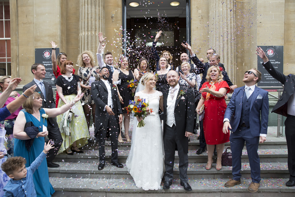 guests throw confetti on bride and groom outside Bristol Register Office