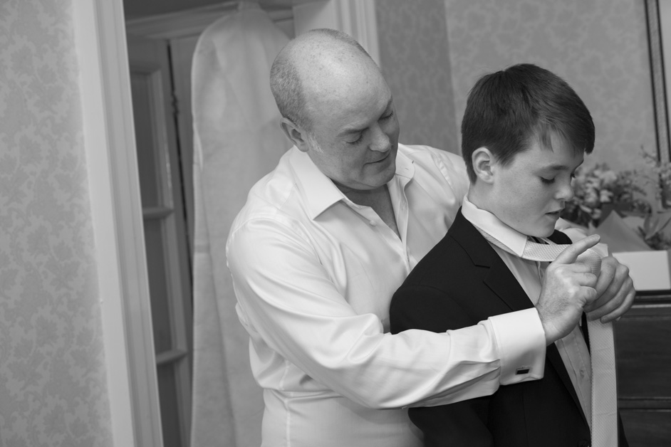groom helping his son with his tie getting ready before the wedding at The Shelleys in Lewes