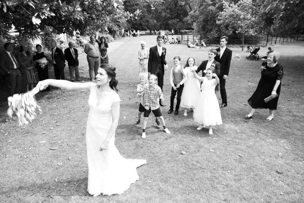 bride throwing the wedding bouquet to children at Lewes Register gardens