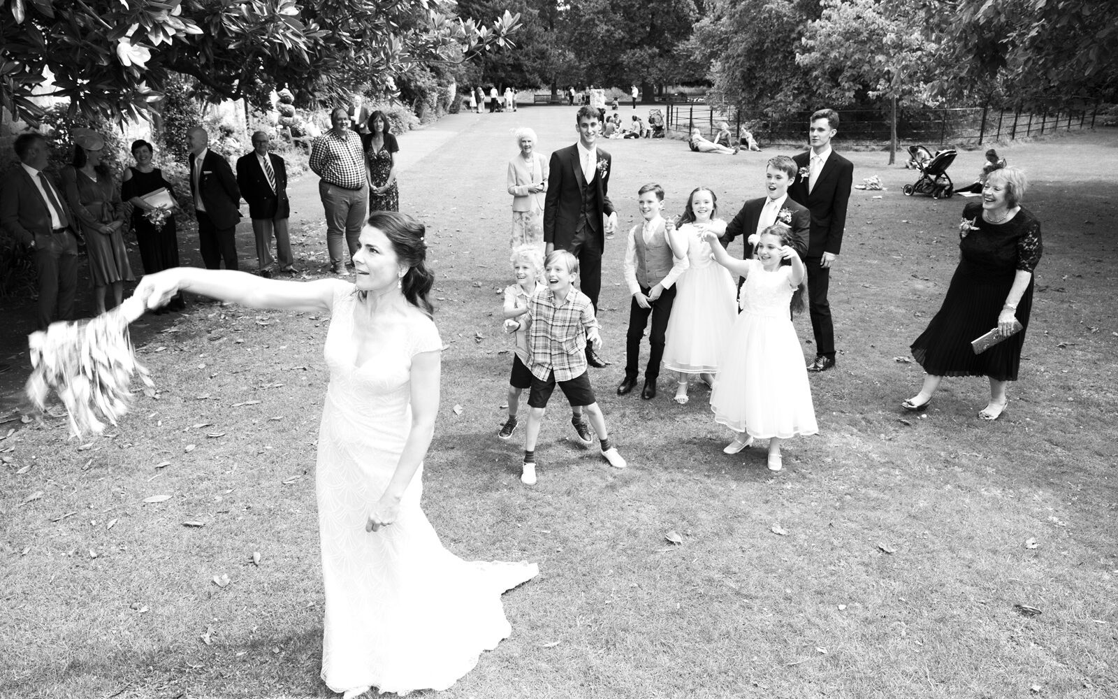 bride throwing the wedding bouquet to children at Lewes Register gardens