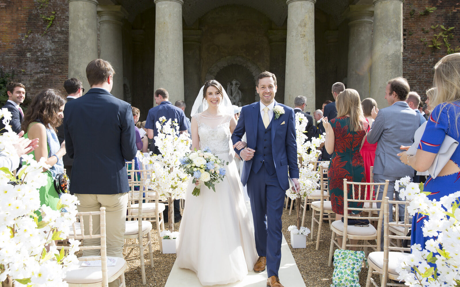 bride and groom walking up the aisle after their outside wedding ceremony at Wotton House in Dorking, Surrey