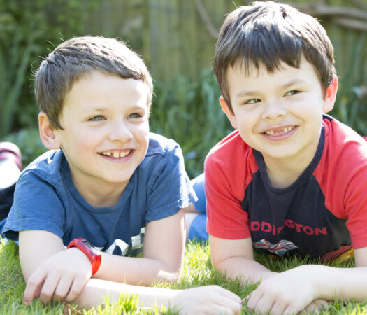 two boys sitting on their tummies smiling in their garden in Tonbridge, Kent. Captured by Kent family portrait photographer Victoria Green