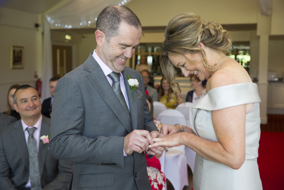 bride and groom laughing exchanging rings at their Weald of Kent wedding in Headcorn
