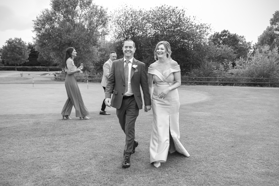 bride and groom walking across the golf course at their Weald of Kent wedding in Kent