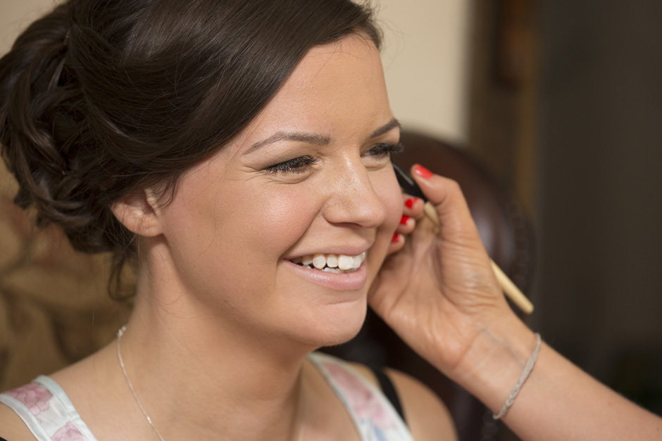 bride having make-up applied during bridal prep at Smarden village home in Kent