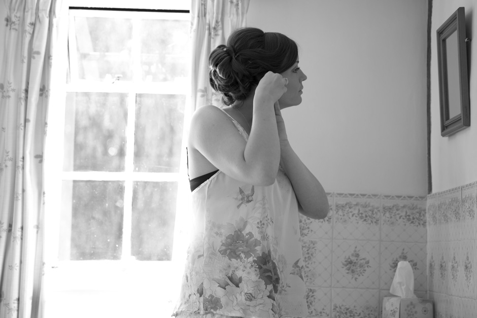 bride putting on earrings looking in the mirror at her Smarden home wedding in Kent