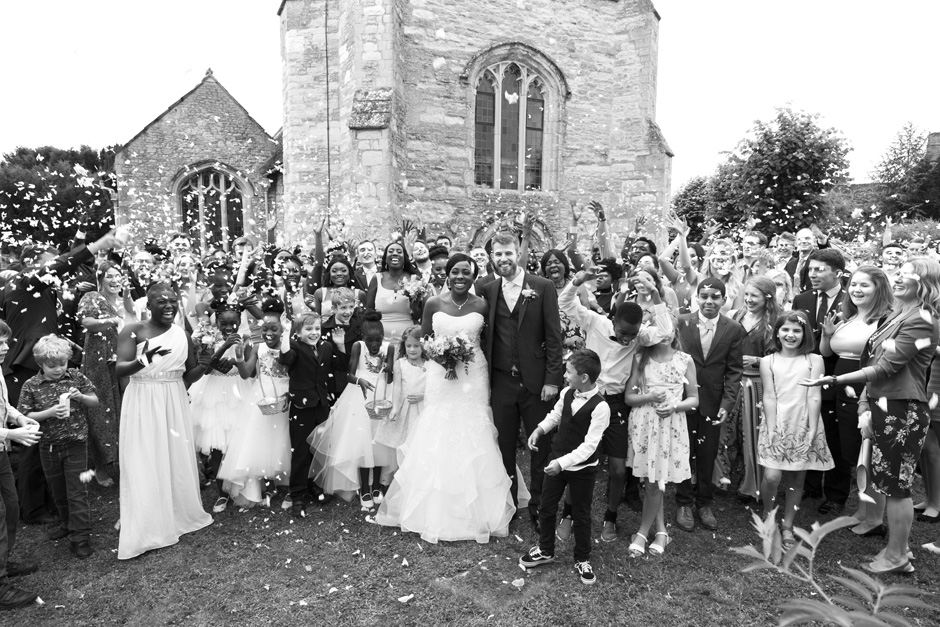 wedding guests throw confetti at bride and groom outside St Nicholas Church at Cuddington Village in Buckinghamshire