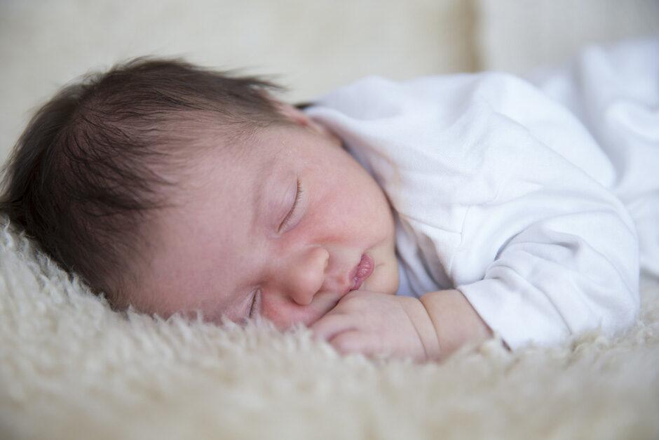 newborn girl sleeping on sheepskin in Tonbridge, Kent
