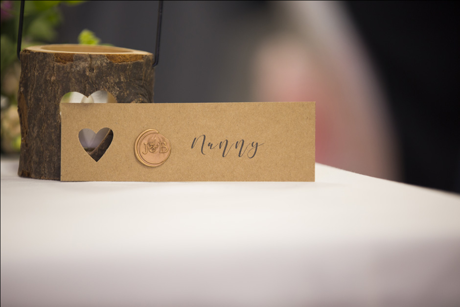 table place setting for 'nanny' with heart cut out and embossed couples' initials at Haddenham Village Hall wedding reception in Buckinghamshire