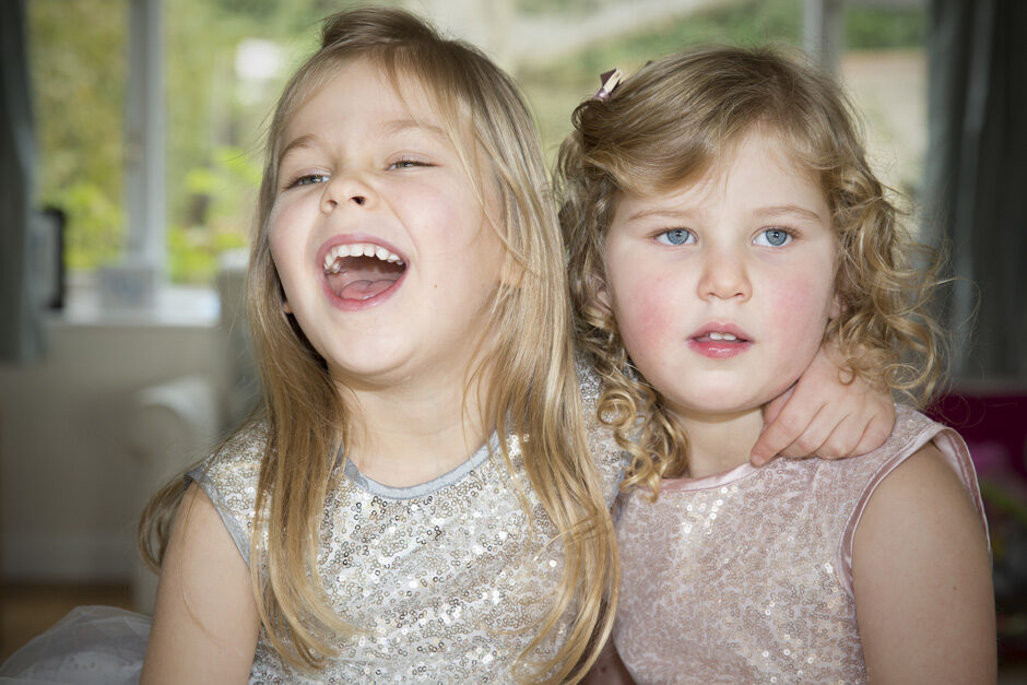 little girls sitting together in sparkly dresses in West Malling, Kent