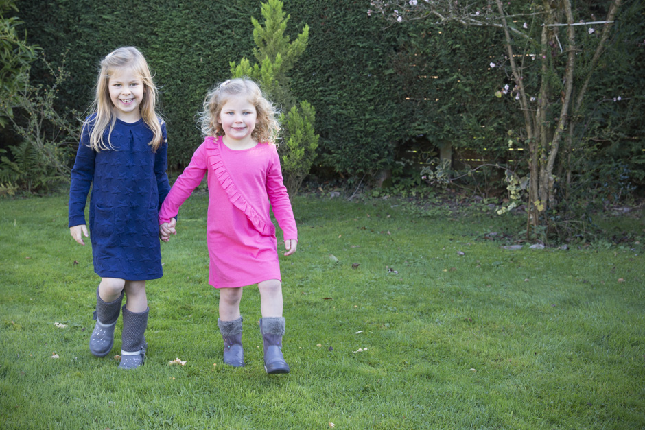 little girls holding hands walking in their garden in West Malling, Kent
