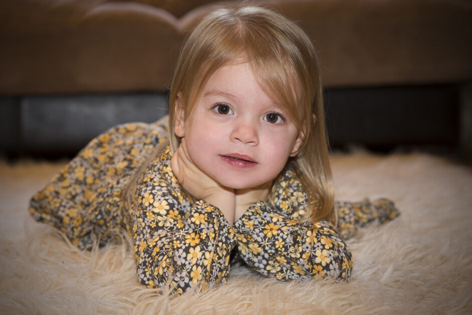 little girl laying on sheepskin on her tummy in Plaxtol, Kent