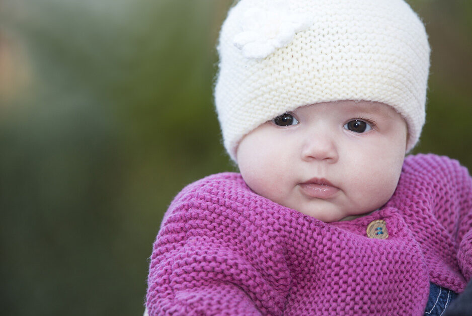 baby girl in wooly hat and pink cardigan in Plaxtol garden, Kent