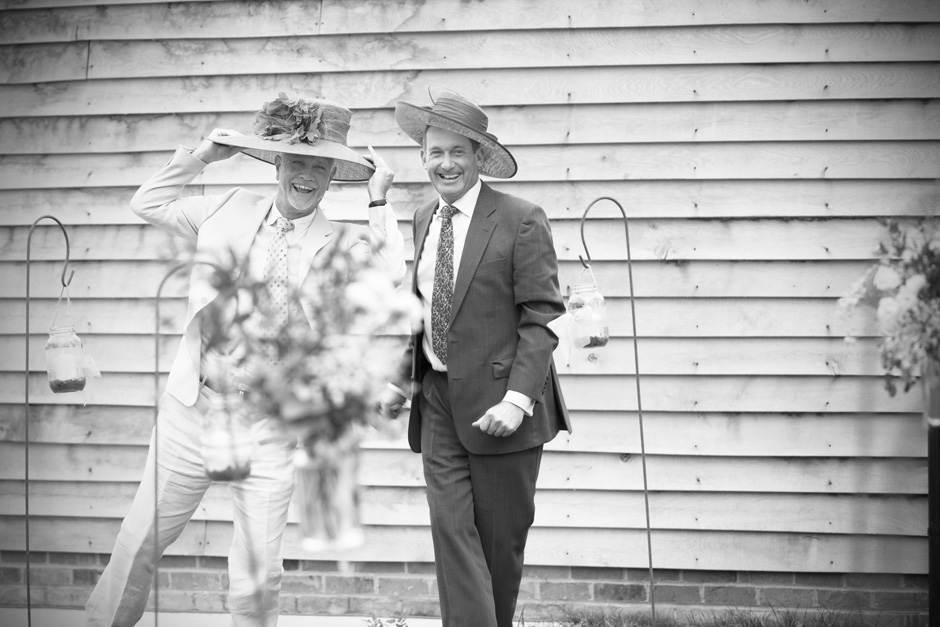 two male guests larking about with ladies hats at Smarden village home wedding in Kent