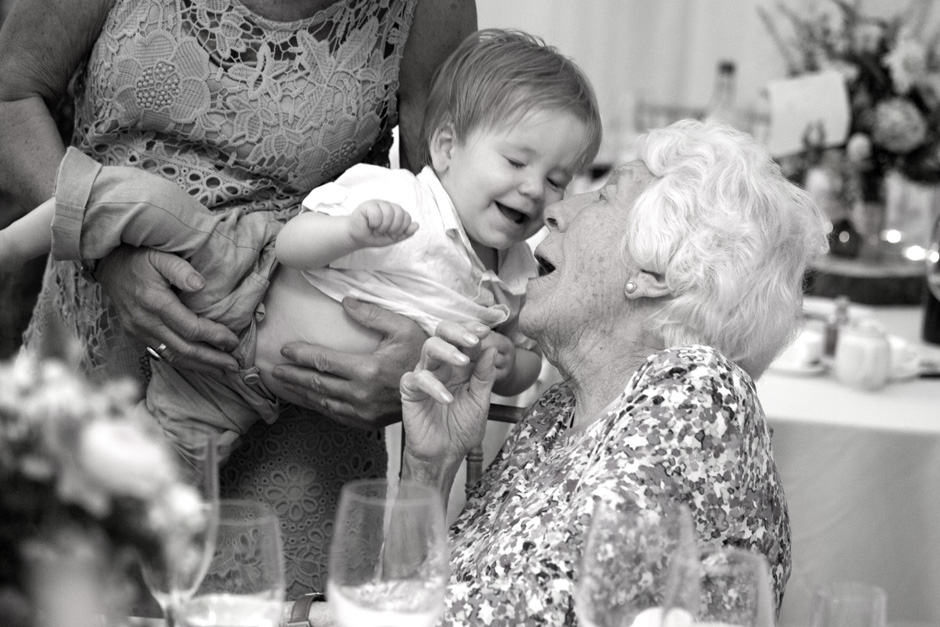 elderly lady making baby laugh at Smarden village home marquee in Kent