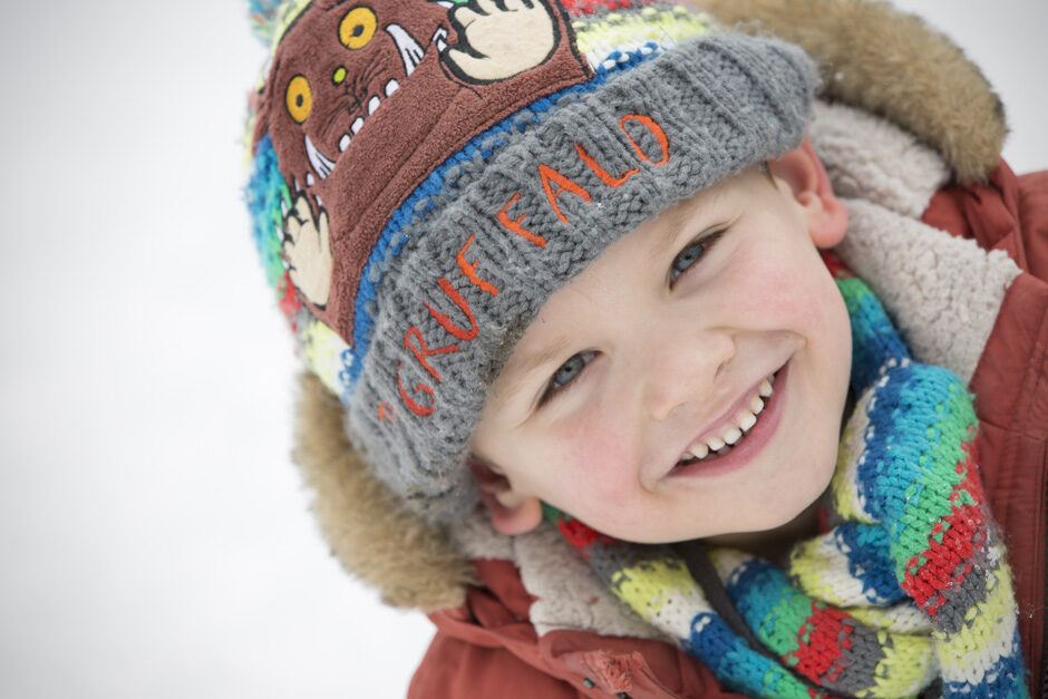 close-up of little boy in scarf and hat in the snow in Tonbridge, Kent
