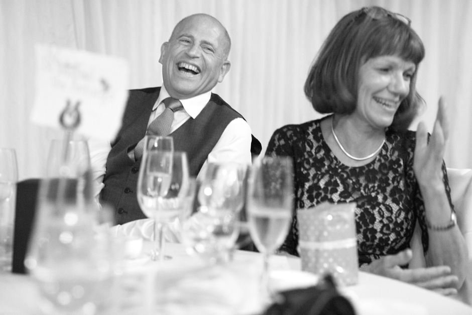 groom's parents laughing during wedding speeches at Smarden village home marquee in Kent