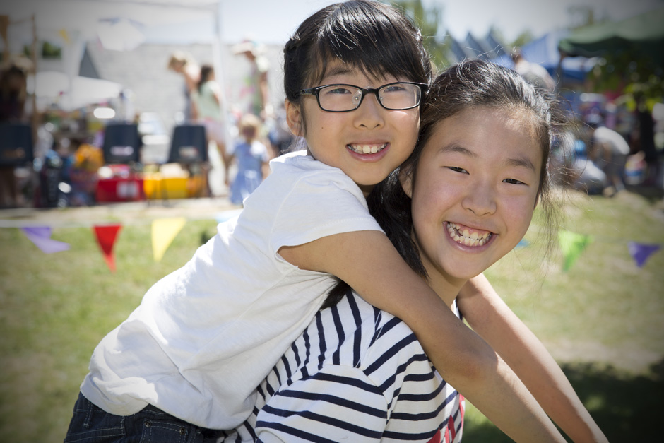 sisters having a piggy back at summer fete in Tonbridge, Kent