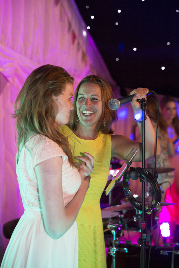 female wedding guests about to sing on microphone during evening wedding reception at Smarden village home marquee in Kent