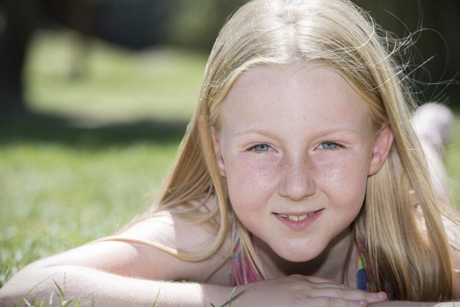little girl sitting on her tummy in the sun in Tonbridge, Kent