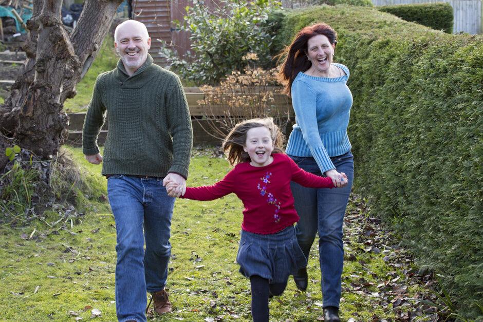 little girl running with her smiling parents in her garden in Tonbridge, Kent