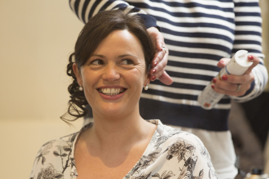 bride smiling while having her hair sprayed during bridal prep at Dale Hill Hotel in Ticehurst, East Sussex