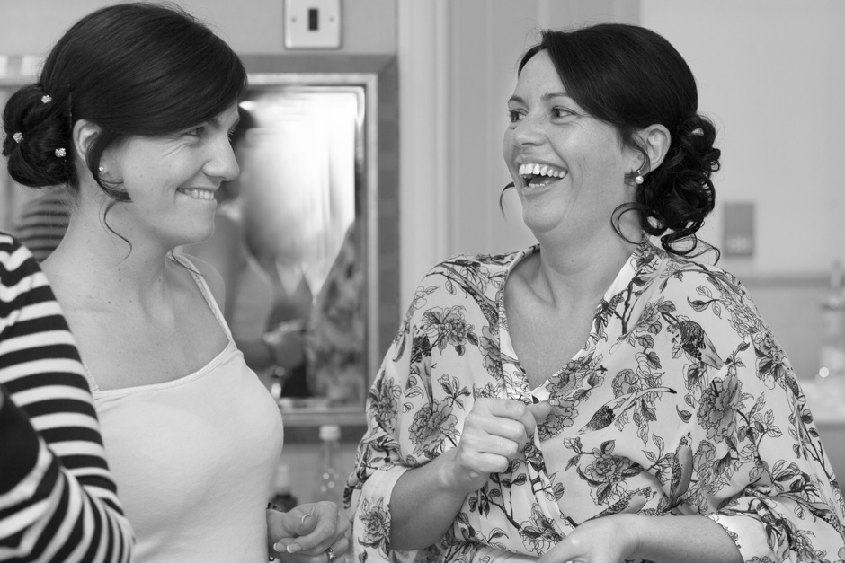 bride laughing with bridesmaid during bridal prep at Dale Hill Hotel in Ticehurst, East Sussex