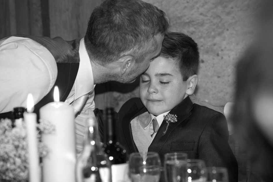 groom kissing little boy best man during wedding speeches at Swallows Oast in Ticehurst, East Sussex