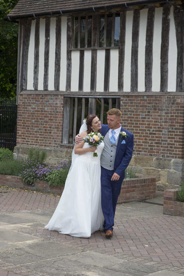 bride and groom walking outside Bridge Cottage in Uckfield