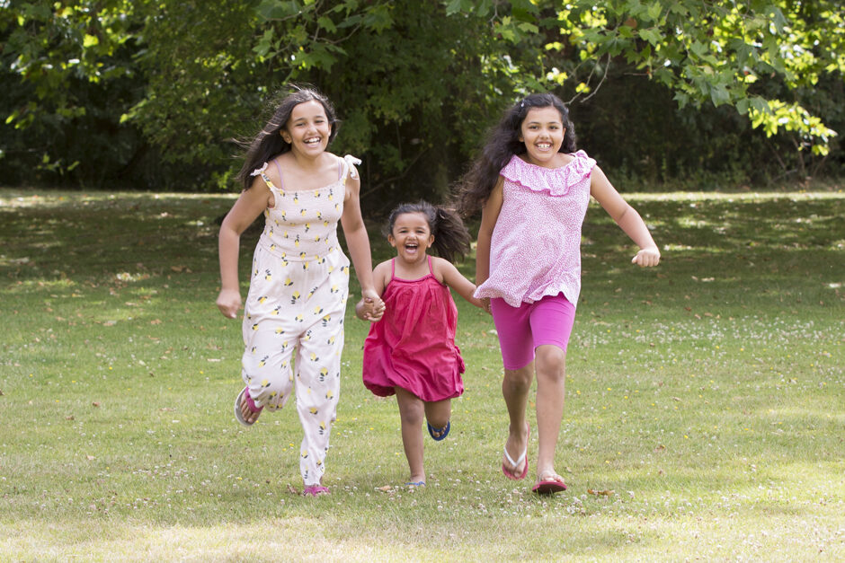 Three little sisters running holding hands captured by Kent family photographer Victoria Green