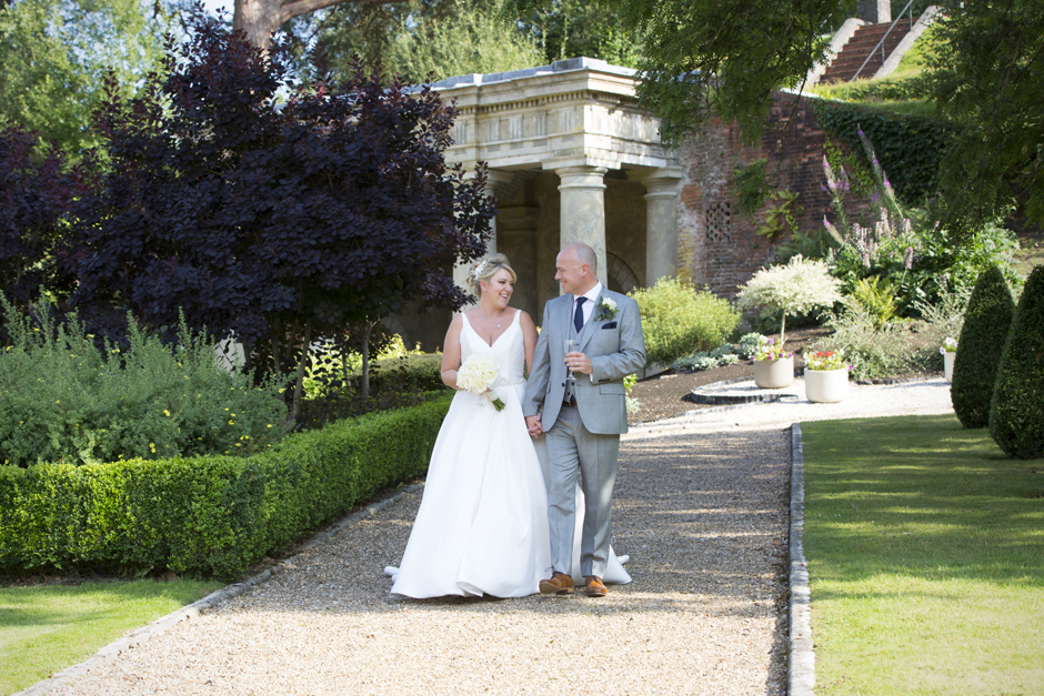 bride and groom walking outside at Wotton House in Dorking, Surrey