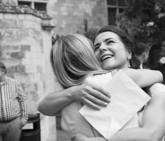bride shares a loving embrace with a friend at Lewes Register Office in East Sussex. Captured by Kent wedding photographer Victoria Green.