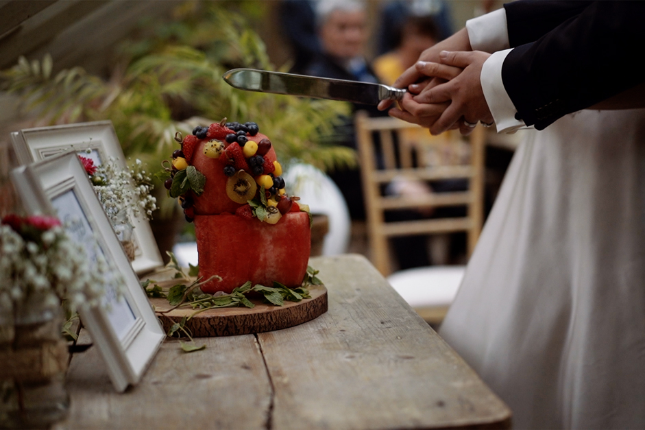Bride and groom sitting cake taken by Kent wedding videographer Aidan Willis