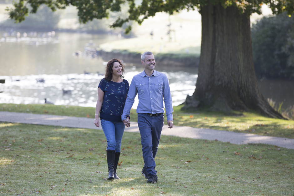 engagement shoot with couple walking through Dunorlan Park with lake in background, Tunbridge Wells in Kent