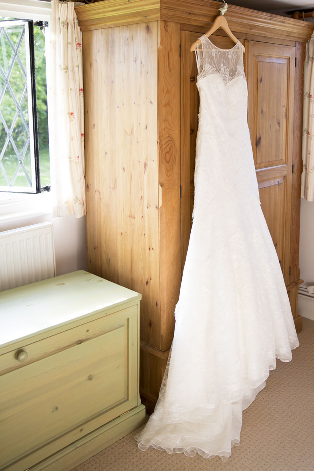 bride's dress hanging on the wardrobe in her bedroom at her Smarden house in Kent