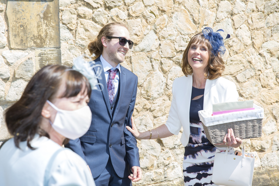 Mother of the bride laughing with guests at St Stephen's Church wedding in Tonbridge, Kent
