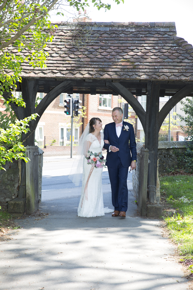 Bride and Father laughing under lynch gate at St Stephen's Church in Tonbridge, Kent