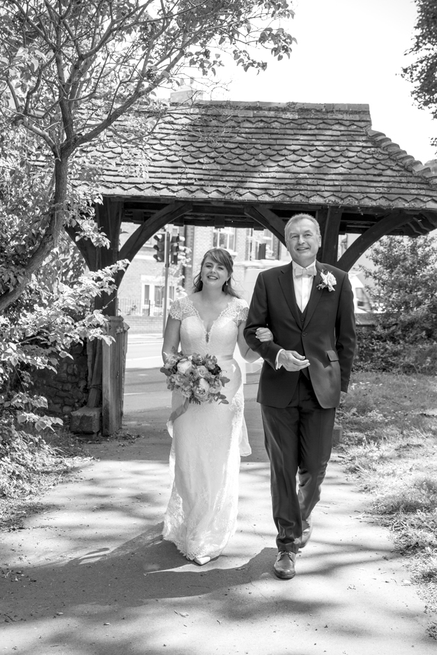 Bride and Bride's Father walking down the church pathway to St Stephen Church, Tonbridge in Kent
