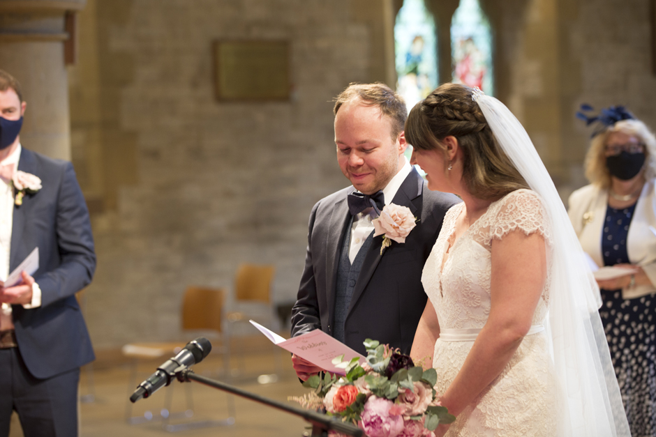Groom and bride laughing reading order of service at St Stephen's Church wedding in Tonbridge, Kent