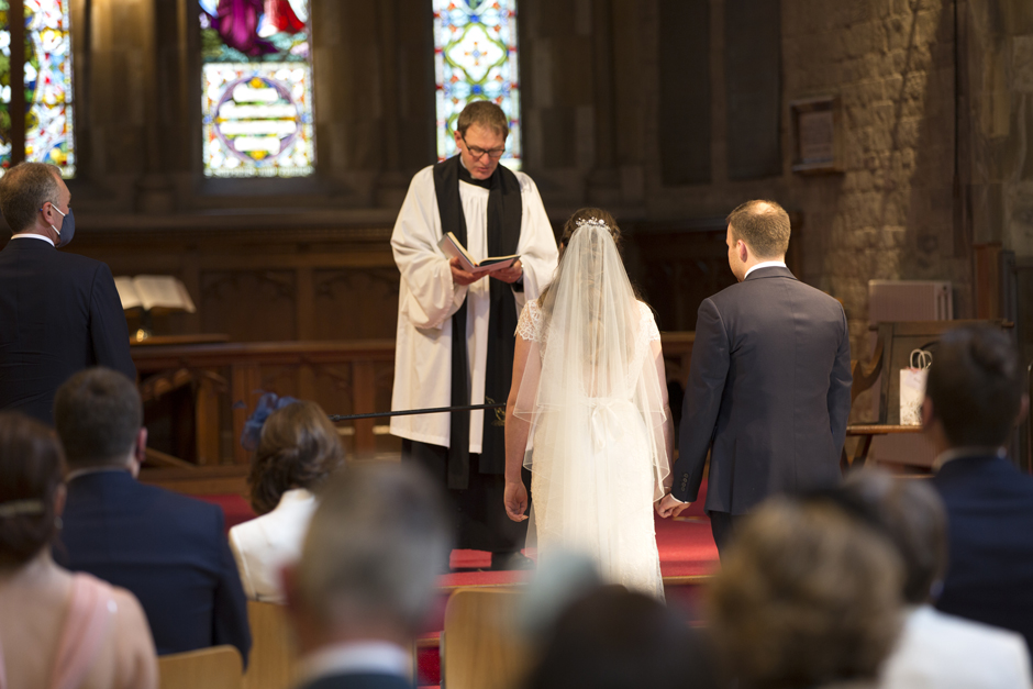 Bride and Groom listening to vicar from behind at St Stephen's Church wedding in Tonbridge, Kent