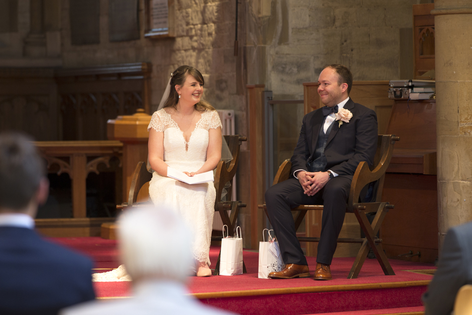 Bride and Groom smiling together during vicar's sermon at St Stephen's Church wedding ceremony in Tonbridge, Kent